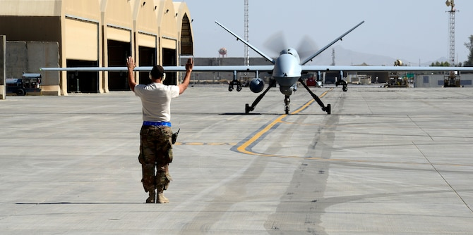 An Airman assigned to the 451st Expeditionary Aircraft Maintenance Squadron marshals an MQ-9 Reaper to its parking spot, March 23, 2018, at Kandahar Airfield, Afghanistan.