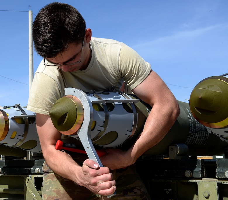 Senior Airman Ethan Dietz, 451st Expeditionary Aircraft Maintenance Squadron conventional maintenance crew member tightens a nose extender on a GBU-38 version one during a GBU-38/V1 build, March 23, 2018, at Kandahar Airfield, Afghanistan.