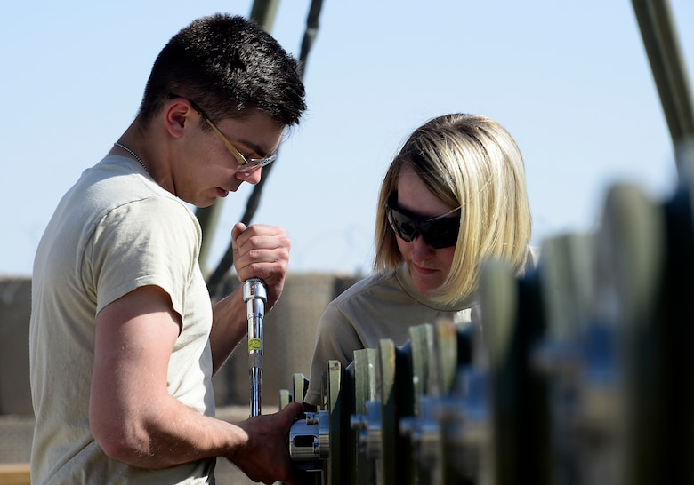 Senior Airman Ethan Dietz and Staff Sgt. Amanda Loyd, 451st Expeditionary Aircraft Maintenance Squadron conventional maintenance crew members, torque a closure ring on the tail fuse of a GBU-38 version one, March 23, 2018, at Kandahar Airfield, Afghanistan.