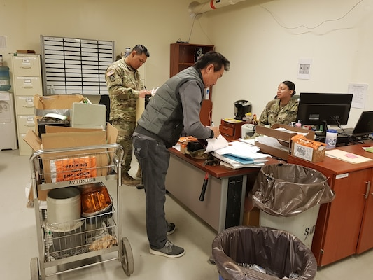 Team member Ki Song Chong (center) educates Army Sgt. John Than (left) and Staff Sgt. Gena Williams from the 602nd Aviation Support Battalion on the proper use of local stock numbers for items that do not have National Stock Numbers.