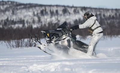 A soldier maneuvers on a snowmobile