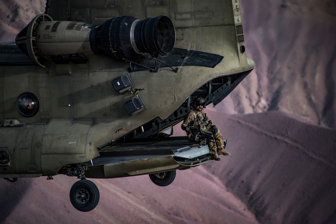 A U.S. Army Task Force Brawler CH-47F Chinook flight engineer sits on the ramp while conducting a training exercise with a Guardian Angel team assigned to the 83rd Expeditionary Rescue Squadron at Bagram Airfield, Afghanistan, March 26, 2018. The Army crews and Air Force Guardian Angel teams conducted the exercise to build teamwork and procedures as they provide joint personnel recovery capability, aiding in the delivery of decisive airpower for U.S. Central Command. (U.S. Air Force Photo by Tech. Sgt. Gregory Brook)