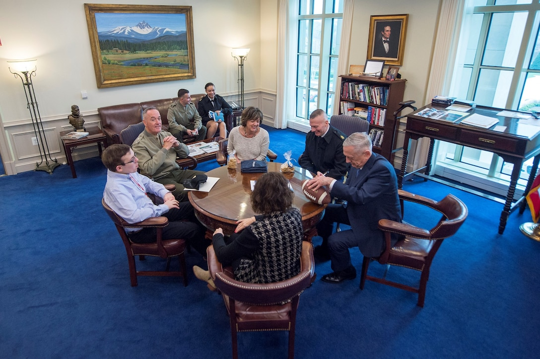 Defense Department leaders sit at a round table with a teenager.