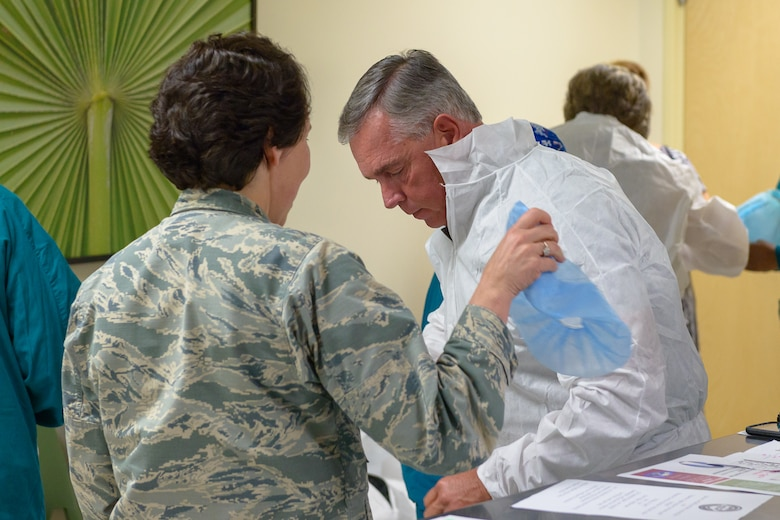 U.S. Air Force Col. Jeannine Ryder, 81st Medical Group commander, assists Jeff Hammond, with his protective clothing during a visit at Keesler Medical Center March 30, 2018, on Keesler Air Force Base, Mississippi. Hammond and Gant spent the day meeting veterans at the Armed Forces Retirement Home and toured various facilities that support veterans on Keesler Air Force Base. Gant is a former NASCAR driver and Hammond is a current TV broadcaster for the motorsport. (U.S. Air Force photo by Andre' Askew)