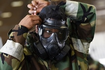 Airman 1st Class Kimani Petersen, a 28th Maintenance Squadron aerospace ground equipment technician, quickly dons his gas mask during chemical, biological, radiological, nuclear and environmental training at Ellsworth Air Force Base, S.D., March 23, 2018. During the course, students learned to properly store and wear mission oriented protective posture gear, cover military assets and test surfaces for chemical agents. (U.S. Air Force photo by Airman 1st Class Donald C. Knechtel)