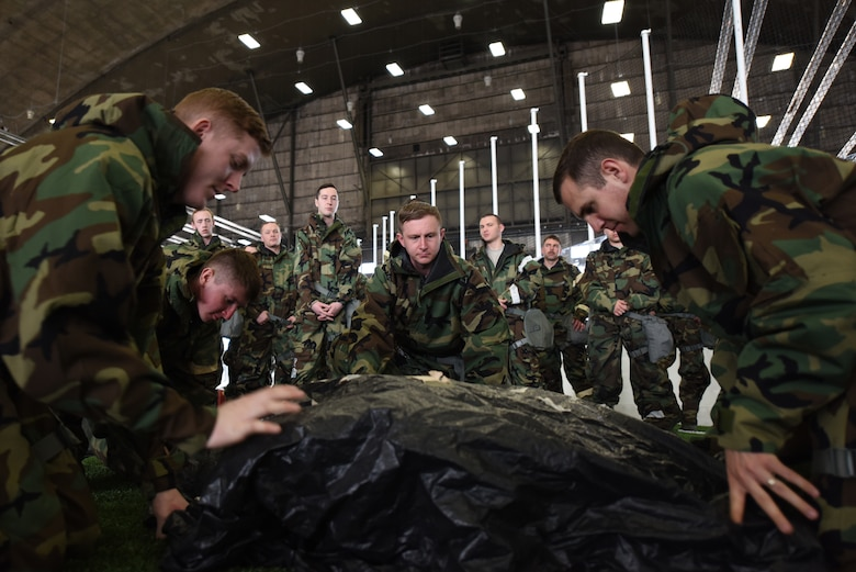 Airmen cover military assets and mark them during chemical, biological, radiological, nuclear and environmental training at Ellsworth Air Force Base, S.D., March 23, 2018. During the course, students learned to properly store and wear mission oriented protective posture gear, cover military assets, and how to test surfaces for chemical agents. (U.S. Air Force photo by Airman 1st Class Donald C. Knechtel)