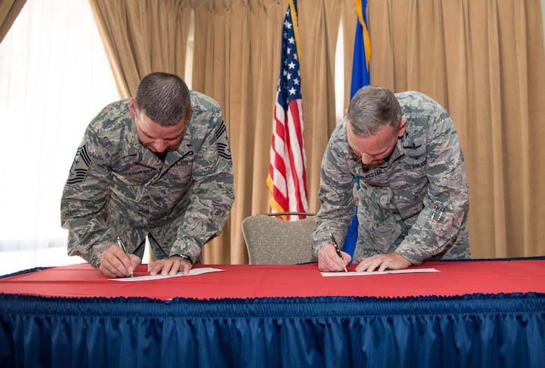 Chief Master Sgt. Randy Kwiatkowski, 56th Fighter Wing command chief, and Col. Robert Sylvester, 56th Mission Support Group commander, sign the Air Force Assistance Fund donation forms during the AFAF campaign kickoff breakfast at Luke Air Force Base, Ariz., April 2, 2018. Kwiatkowski and Sylvester made their initial contributions to the AFAF, officially starting the six-week campaign at Luke. (U.S. Air Force photo by Airman 1st Class Alexander Cook)