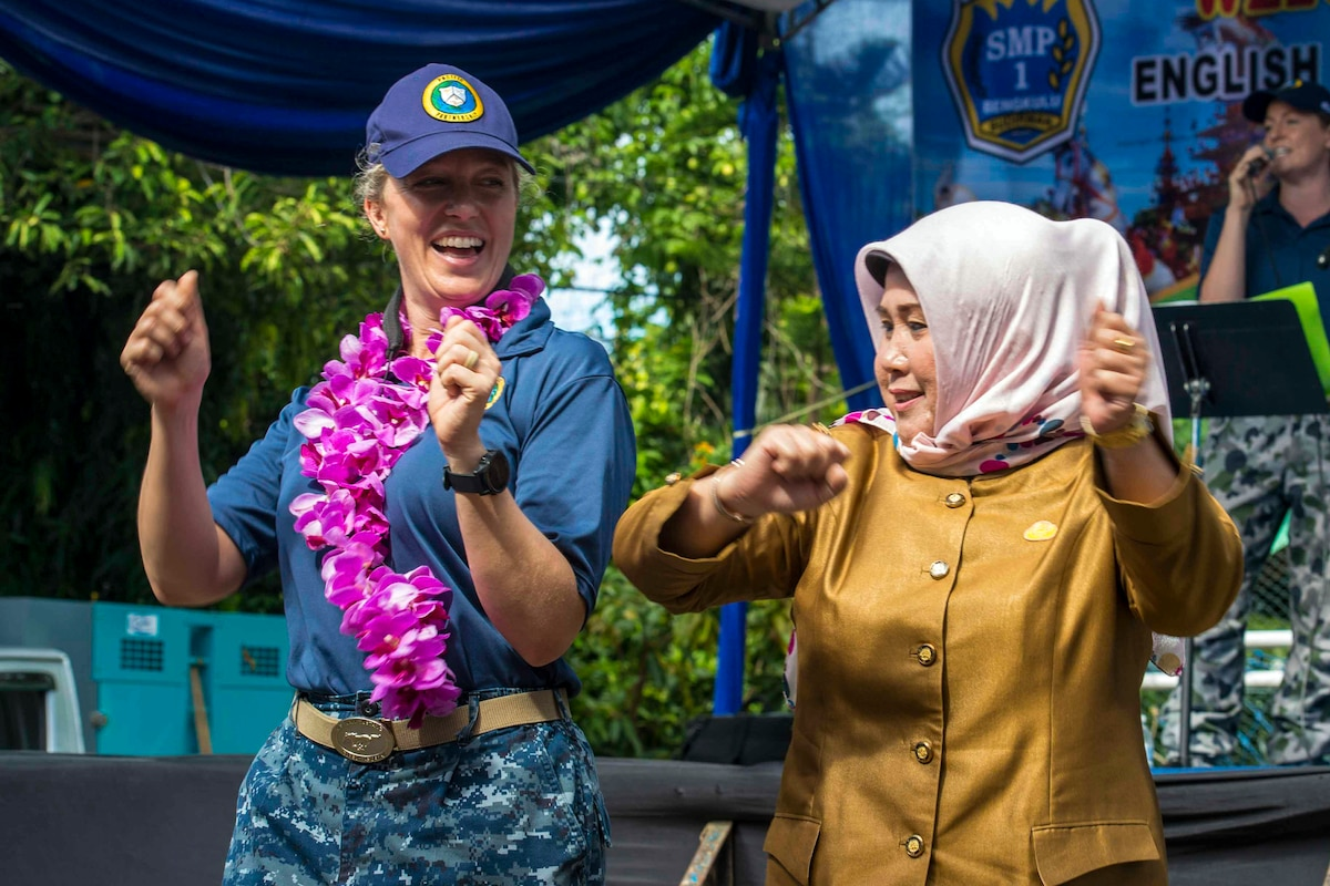 A sailor wearing a lei dances with a woman wearing a headscarf.
