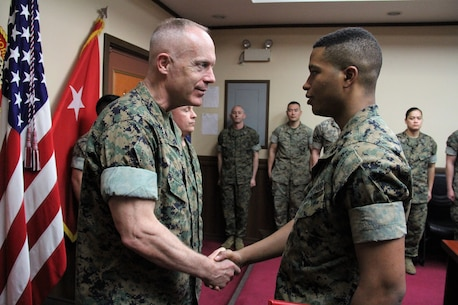 Maj. Gen. Patrick J. Hermesmann (left), commander of U.S. Marine Corps Forces Korea, congratulates Lance Cpl. Elijah A. Williamson, MARFORK G-5 Plans and Policy clerk, after promoting him to his current rank here, April 2.  According to Hermesmann, Williamson has received considerable accolades for his work in supporting the command's mission. (Official U.S. Marine Corps photo by Sgt. Nathaniel Hanscom/Released)