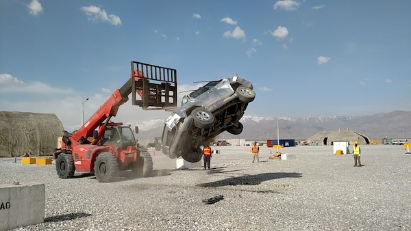 Personnel use a large forklift to lift a vehicle and let it roll after being dropped to shake loose any ammunition that may have been left behind in the vehicles before any unfired rounds can cause an accident during disposal.