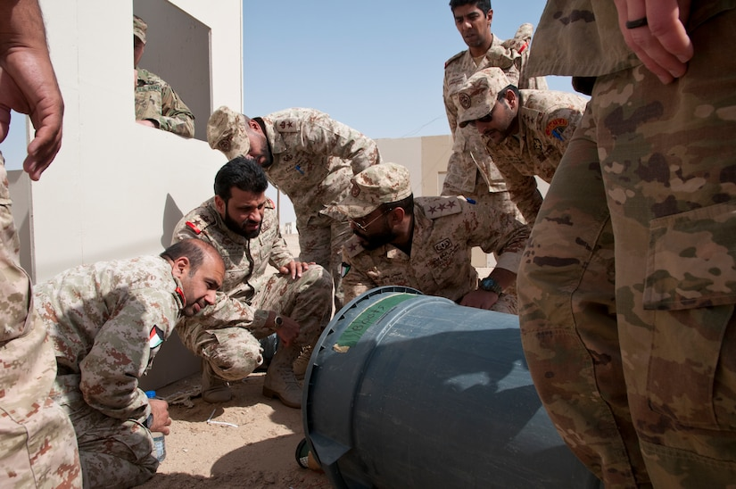 Kuwait Land Force explosive ordnance disposal-qualified officers discuss tactics and techniques for defeating improvised explosive devices during joint training with U.S. EOD technicians at Udari Range Complex near Camp Buehring, Kuwait, March 22, 2018. Army photo by Sgt. David L. Nye