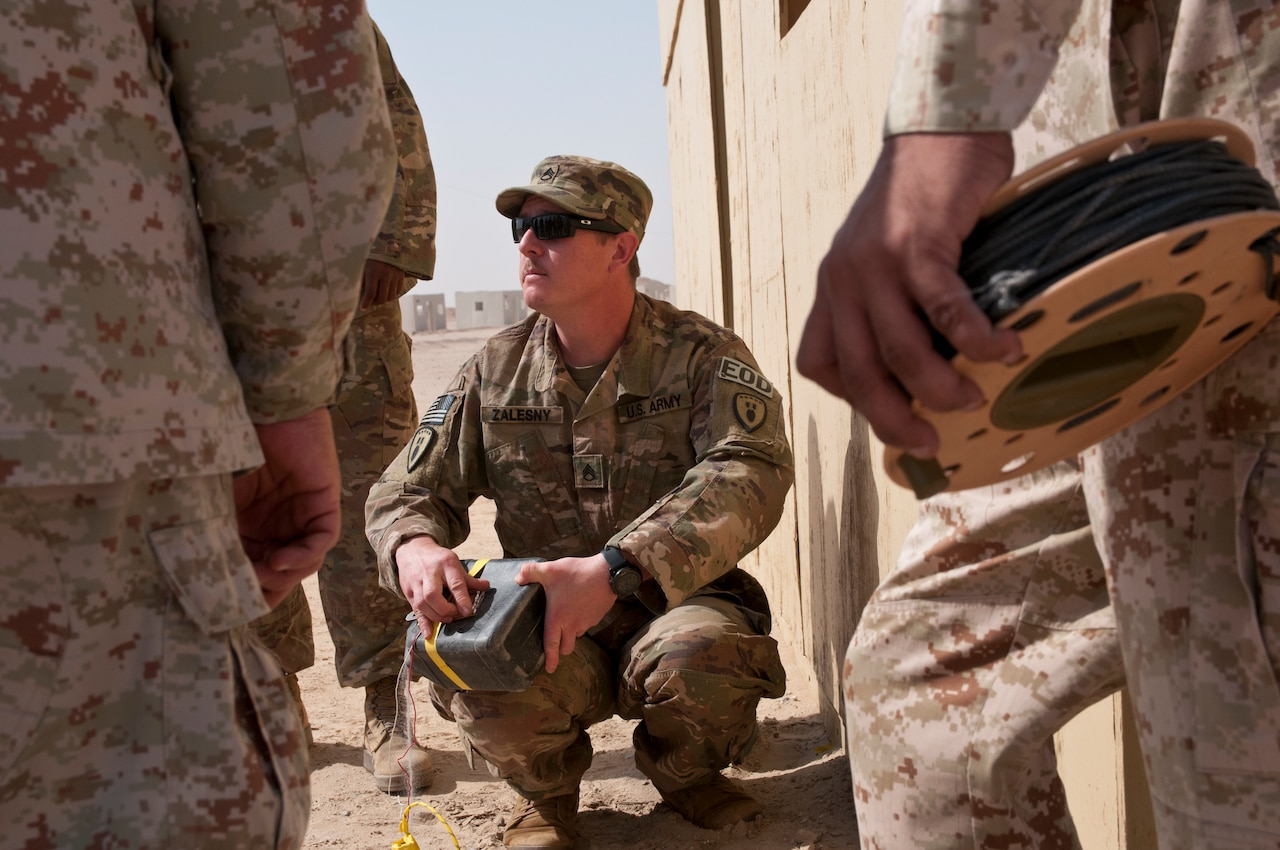 Army Staff Sgt. Zachary Zalesny, an explosive ordnance disposal technician with the 797th Ordnance Company, discusses techniques to defeat improvised explosive devices during a joint training exercise with Kuwait Land Force officers at Udari Range Complex near Camp Buehring, Kuwait, March 22, 2018. Army photo by Sgt. David L. Nye