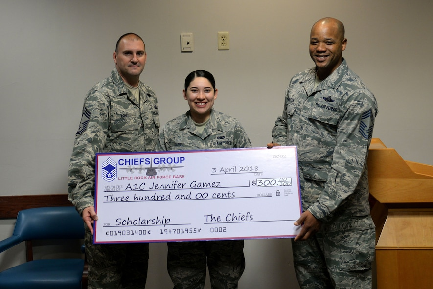 A woman in the Airman Battle Uniform holds a giant check with two men in Airman Battle Uniforms.