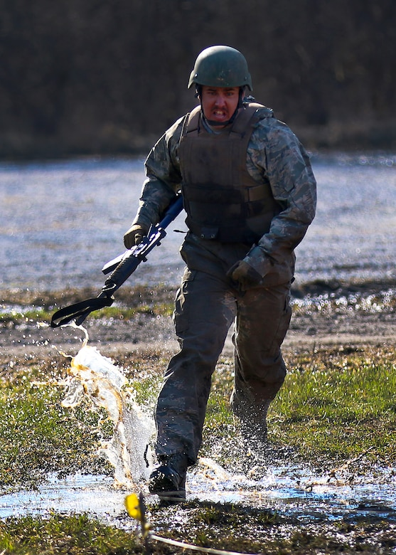 Staff Sgt. Anthony Wilson, 445th Security Forces Squadron, runs through mud and grass as he prepares to go into a low crawl during the 2018 Winter Challenge held during the March 2, 2018 unit training assembly.
