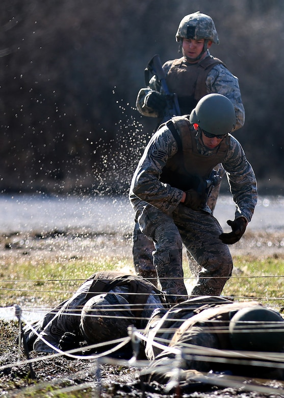 Staff Sgts. Tyler Heath (top) and Jonathan Prather, 445th Security Forces Squadron, prepare to hit the ground with purpose as they go into a low crawl under wire during the winter challenge exercise March 2, 2018