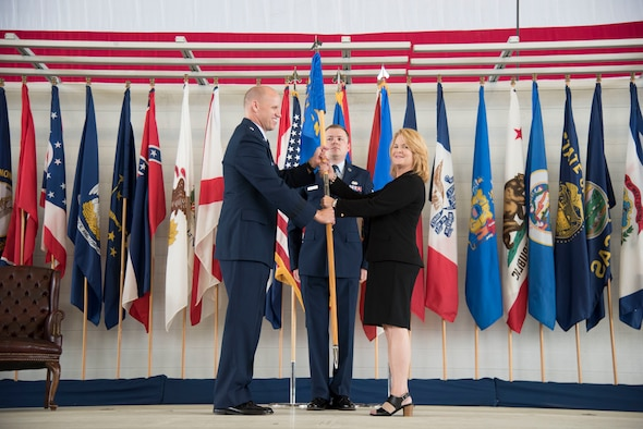 Brig. Gen. Evan Dertien, 96th Test Wing commander, hands the 96th Range Group guidon to the unit's new director, Jeri McClung during a March 28 ceremony at Eglin Air Force Base, Fla. McClung is no stranger to the group, having served in various within as well as outside the organization. The 96th RG is responsible for the planning and execution of flight, ground and laboratory test missions. (U.S. Air Force Photo/Jasmine Porterfield)