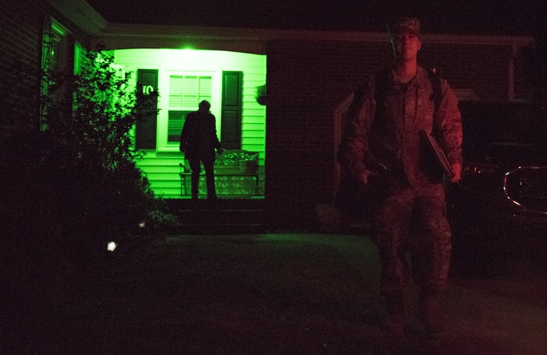 U.S. Air Force Airman 1st Class Nicholas Whitehurst, 633rd Communications Squadron client systems technician, departs for the airport as his mom, Amy, follows behind, illuminated by their green porch light in Hampton, Virginia, March 27, 2018.