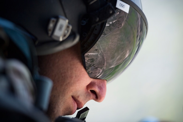 Tech. Sgt. Brandon Garbrick, 71st Rescue Squadron HC-130J Combat King II loadmaster, looks out of the door of an HC-130J during Tiger Rescue IV, March 27, 2018, at Vandenberg Air Force Base, Calif.  The four-day exercise challenged Airmen from multiple rescue squadrons to bring the capabilities of the personnel recovery triad together to successfully complete rescue missions and maintain proficiency. The three branches of the personnel recovery triad are the HC-130J, HH-60G Pave Hawk and the guardian angel weapons system or pararescuemen. (U.S. Air Force photo by Senior Airman Janiqua P. Robinson)