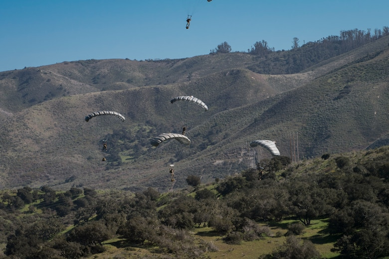 Pararescuemen from the 58th Rescue Squadron Nellis Air Force Base, Nev.,  descend onto a drop zone during Tiger Rescue IV, March 28, 2018, at Vandenberg Air Force Base, Calif. The four-day exercise challenged Airmen from multiple rescue squadrons to bring the capabilities of the personnel recovery triad together to successfully complete rescue missions and maintain proficiency. The three branches of the personnel recovery triad are the HC-130J Combat King II, HH-60G Pave Hawk and the guardian angel weapons system or pararescuemen. (U.S. Air Force photo by Senior Airman Janiqua P. Robinson)