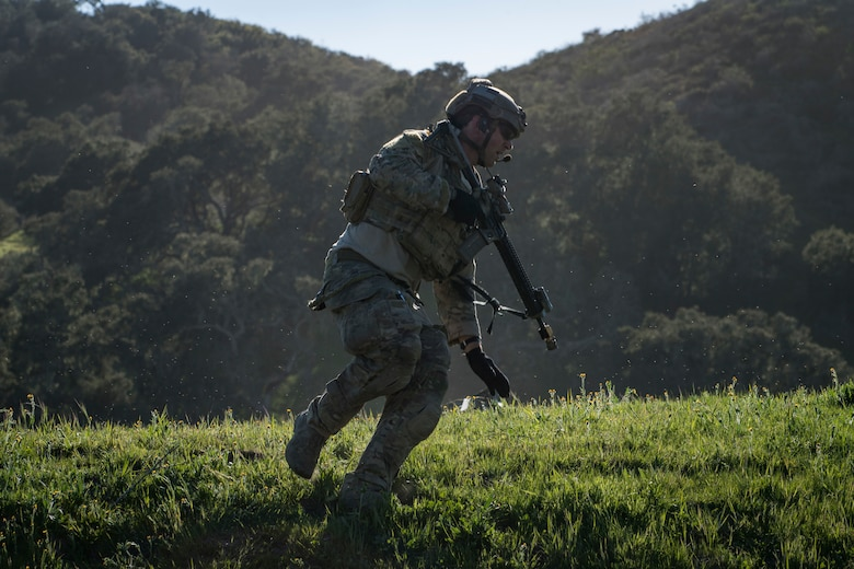 A pararescueman from the 58th Rescue Squadron, Nellis Air Force Base, Nev., runs for cover during Tiger Rescue IV, March 28, 2018, at Vandenberg Air Force Base, Calif. The four-day exercise challenged Airmen from multiple rescue squadrons to bring the capabilities of the personnel recovery triad together to successfully complete rescue missions and maintain proficiency. The three branches of the personnel recovery triad are the HC-130J Combat King II, HH-60G Pave Hawk and the guardian angel weapons system or pararescuemen. (U.S. Air Force photo by Senior Airman Janiqua P. Robinson)