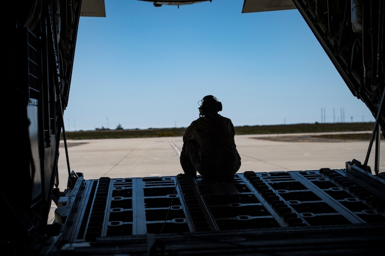 Tech. Sgt. Brandon Garbrick, 71st Rescue Squadron HC-130J Combat King II loadmaster, sits on the ramp of an HC-130J during Tiger Rescue IV, March 27, 2018, at Vandenberg Air Force Base, Calif. The four-day exercise challenged Airmen from multiple rescue squadrons to bring the capabilities of the personnel recovery triad together to successfully complete rescue missions and maintain proficiency. The three branches of the personnel recovery triad are the HC-130J, HH-60G Pave Hawk and the guardian angel weapons system or pararescuemen. (U.S. Air Force photo by Senior Airman Janiqua P. Robinson)