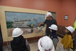 "Old Hickory Dam Power Plant Superintendent Joseph Conatser explains how water from the reservoir enters gate-controlled intakes into the powerhouse, rotates the turbines, spins the turbines and produce the electric current.  A total of 36 kids visited the power plant March 30, 2018 in Hendersonville, Tenn., for ""Bring Your Kids to Work Day."" (USACE Photo by Lee Roberts)"