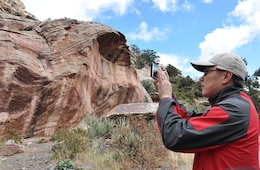 A U.S. Army Corps of Engineers geologist takes a picture of clay imprints on a canyon wall – a predictor indicating that previous pre-historic flood levels had not risen to that height in hundreds, or perhaps, thousands of years – during a paleoflood exercise March 15 at the Red Rock Canyon National Conservation Area near Las Vegas.