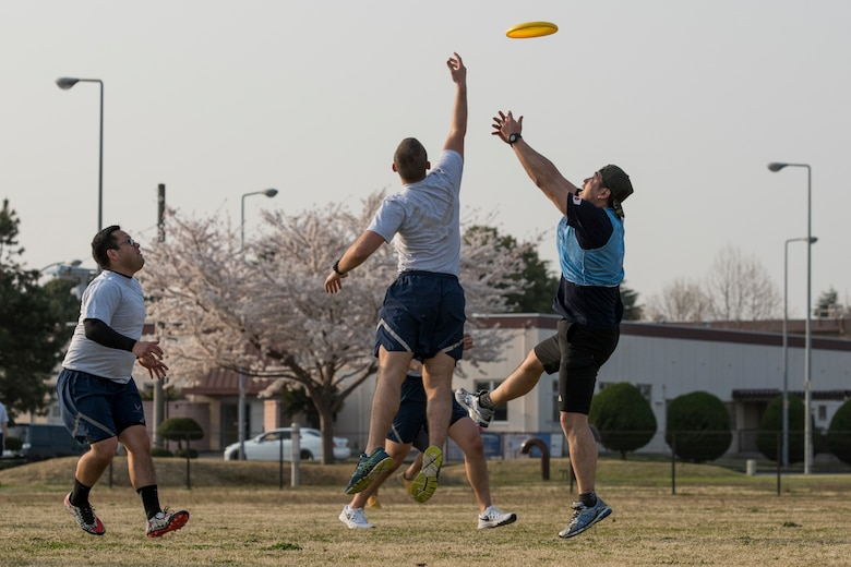 Opposing team members reach for the disk during an ultimate frisbee match, March 28, 2018, at Yokota Air Base, Japan.