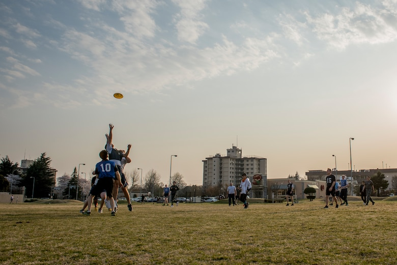 Players reach for a disk during an ultimate frisbee match, March 28, 2018, Yokota Air Base, Japan.