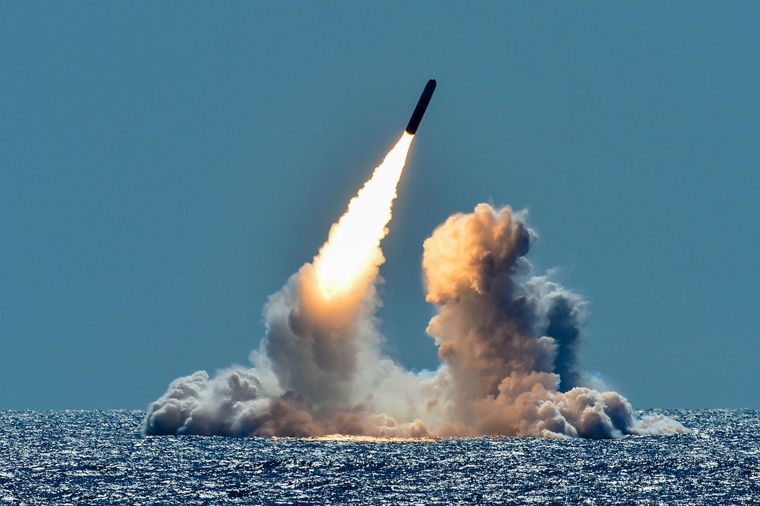 A missile fires out of the ocean at a diagonal trajectory, causing smoke to waft up from the blue water.
