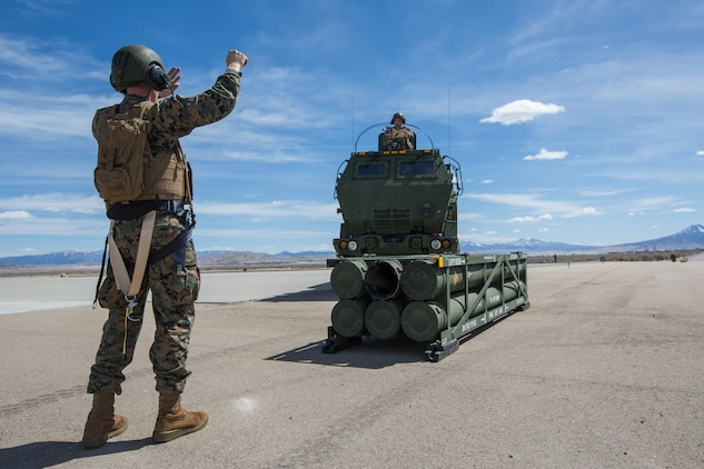 Marine Corps Sgt. Jeffery Hale, a launcher chief with Kilo Battery, 2nd Battalion, 14th Marine Regiment, directs a Marine Corps an M142 High Mobility Artillery Rocket System (HIMARS) into position to pick up missile pods, at Dugway Proving Grounds, Utah, March 30, 2018. Marines from Kilo Battery flew from Fort Campbell, Ky., to Dugway where they offloaded and fired four HIMARS missiles, demonstrating a unique capability that will give commanders more options to deal with threats when other options are not appropriate. (Marine Corps photo by Lance Cpl. Niles Lee)
