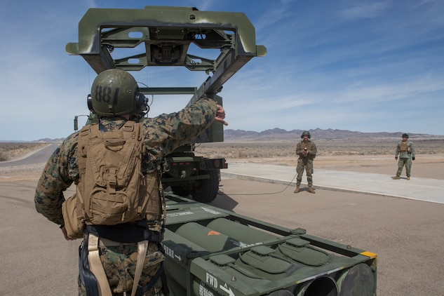 Marine Corps Sgt. Jeffery Hale, a launcher chief with Kilo Battery, 2nd Battalion, 14th Marine Regiment, signals for Cpl. Kyle Thompson, a gunner with Kilo Battery, to lower the hoist on an M142 High Mobility Artillery Rocket System (HIMARS) to pick up missile pods, at Dugway Proving Grounds, Utah, March 30, 2018. Marines from Kilo Battery flew from Fort Campbell, Ky., to Dugway where they offloaded and fired four HIMARS missiles, demonstrating a unique capability that will give commanders more options to deal with threats when other options are not appropriate. (Marine Corps photo by Lance Cpl. Niles Lee)