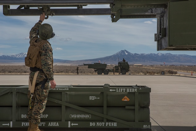 Marine Corps Sgt. Jeffery Hale, a launcher chief with Kilo Battery, 2nd Battalion, 14th Marine Regiment, guides a hoist up on an M142 High Mobility Artillery Rocket System (HIMARS) after dropping off a missile pod, at Dugway Proving Grounds, Utah, March 30, 2018. Marines from Kilo Battery flew from Fort Campbell, Ky., to Dugway where they offloaded and fired four HIMARS missiles, demonstrating a unique capability that will give commanders more options to deal with threats when other options are not appropriate. (Marine Corps photo by Lance Cpl. Niles Lee)