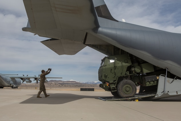 Air Force Staff Sgt. Josh Monroe, a loadmaster from 9th Special Operations Squadron, loads a Marine Corps M142 High Mobility Artillery Rocket System (HIMARS) from Kilo Battery, 2nd Battalion, 14th Marine Regiment, into an Air Force MC-130 at Dugway Proving Grounds, Utah, March 30, 2018. Marines from Kilo Battery flew from Fort Campbell, Ky., to Dugway where they offloaded and fired four HIMARS missiles, demonstrating a unique capability that will give commanders more options to deal with threats when other options are not appropriate. (Marine Corps photo by Lance Cpl. Niles Lee)