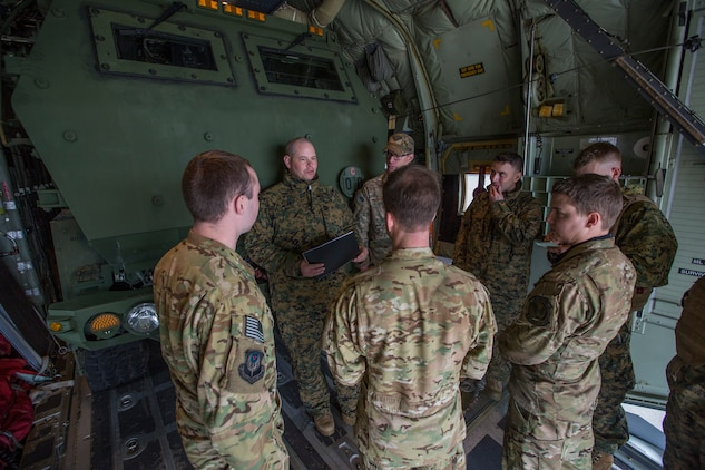 Airmen from 9th Special Operations Squadron and Marines from Kilo Battery, 2nd Battalion, 14th Marine Regiment, discuss flight plans at Fort Campbell, Ky., March 29, 2018. Marines from Kilo Battery used an Air Force MC-130 to conduct a live-fire raid at Dugway Proving Ground, Utah, flying from Fort Campbell, to Dugway. There, they offloaded and fired four HIMARS missiles, demonstrating a unique capability that will give commanders more options to deal with threats when other options are not appropriate. (Marine Corps photo by Lance Cpl. Niles Lee)
