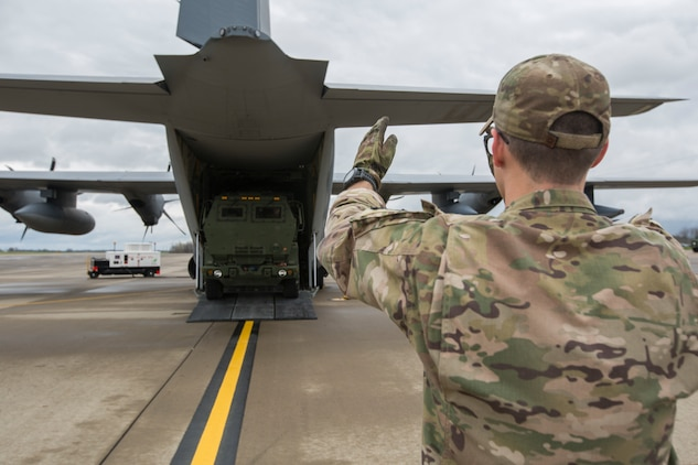 Air Force Staff Sgt. Josh Monroe, a loadmaster from 9th Special Operations Squadron, off loads a Marine Corps M142 High Mobility Artillery Rocket System (HIMARS) from an Air Force MC-130 at Fort Campbell, Ky., March 29, 2018. Marines from Kilo Battery used an Air Force MC-130 to conduct a live-fire raid at Dugway Proving Ground, Utah, flying from Fort Campbell, to Dugway. There, they offloaded and fired four HIMARS missiles, demonstrating a unique capability that will give commanders more options to deal with threats when other options are not appropriate. (Marine Corps photo by Lance Cpl. Niles Lee)