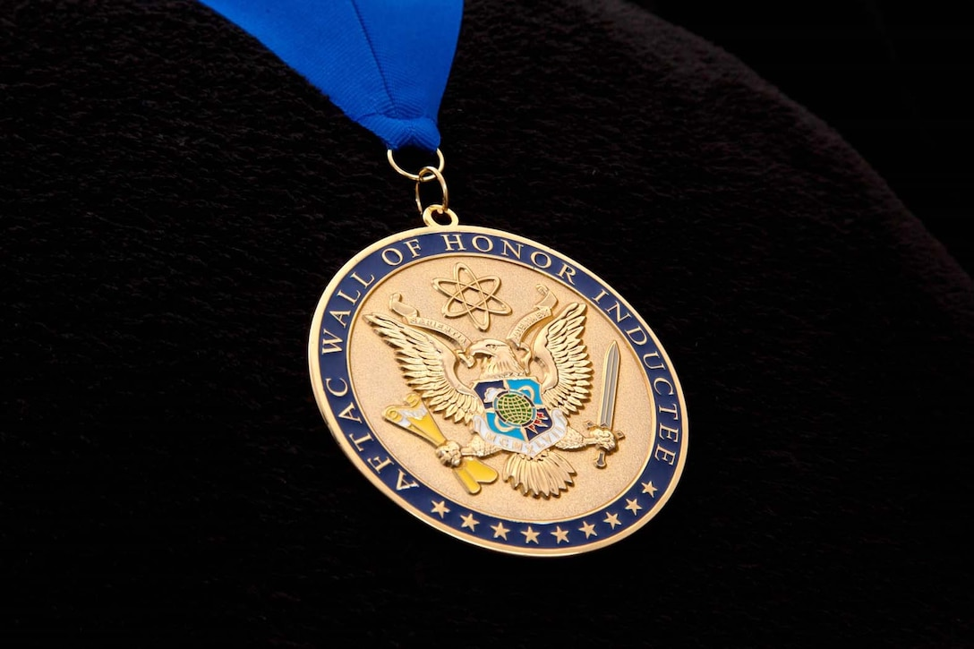 """Three medallions were presented to the 2018 Wall of Honor inductees at the Air Force Technical Applications Center, Patrick AFB, Fla.  The medallion, which was created by 1st Lt. Adam Satterfield and Master Sgt. Chad Taguba, both members of AFTAC, symbolizes the 12 inductees' contributions to long range detection and nuclear treaty monitoring, AFTAC's primary mission.  The back of the medallion has a personalized inscription that reads, """"Let this medallion signify its recipient is a member of an elite and noble group of Airmen who stand in silent vigil for the good of all humankind.""""  (U.S. Air Force photo by Master Sgt. Chad Taguba)"""