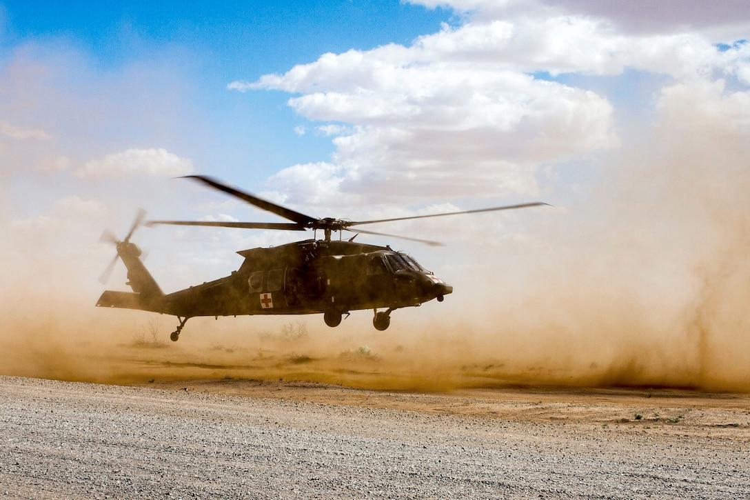 A UH-60 Black Hawk helicopter lands.