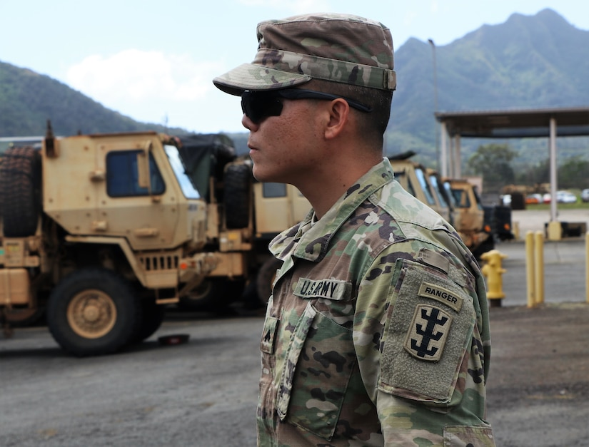 Soldier poses near the vehicles he maintains.
