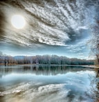 clouds and tree reflected on lake