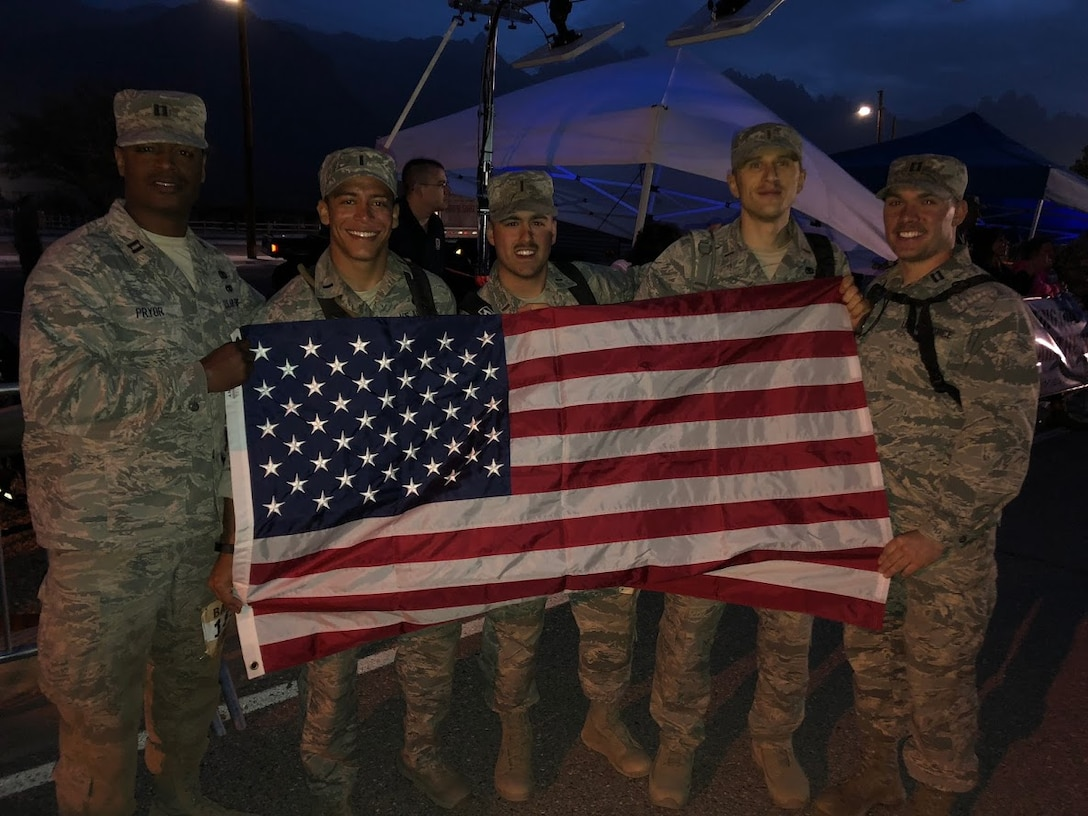 A team from Altus Air Force Base, Okla. holds up the American Flag after making it to the finish line of the 29th annual Bataan Memorial Death March, March 25, 2018, at White Sands, N.M.