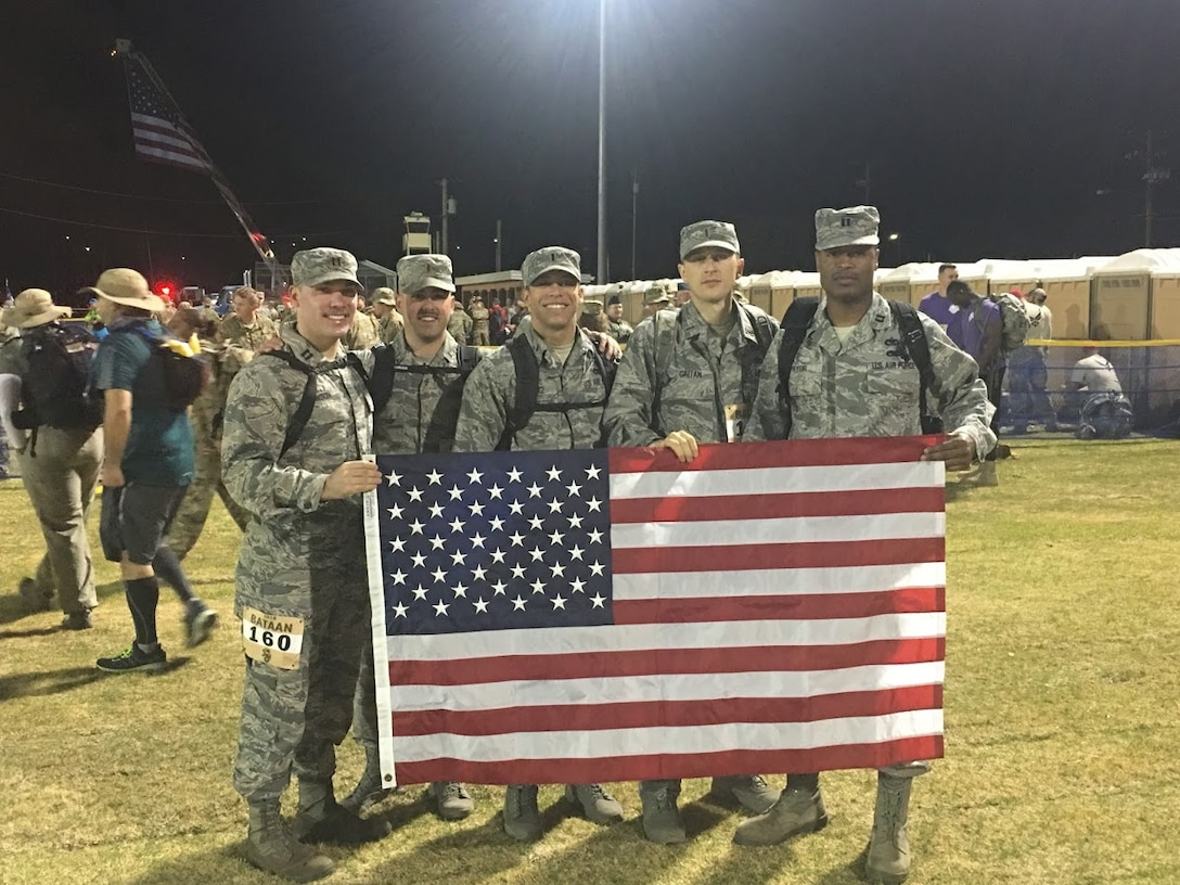 A team from Altus Air Force Base, Okla. holds up the American Flag before participating in the 29th annual Bataan Memorial Death March, March 25, 2018, at White Sands, N.M.