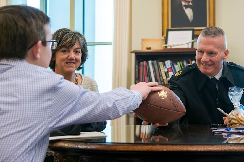 Army Command Sgt. Maj. John W. Troxell, senior enlisted advisor to the chairman of the Joint Chiefs of Staff, hands a football to a civilian