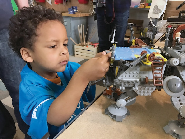 Three-year-old Sam Slentz-Bobo works on a Lego robot during the ribbon cutting ceremony for the new Center of Innovation at Kirtland Youth Programs on Thursday, March 29. The center was constructed using a $45,000 grant from Raytheon and the Boys and Girls Clubs of America.
