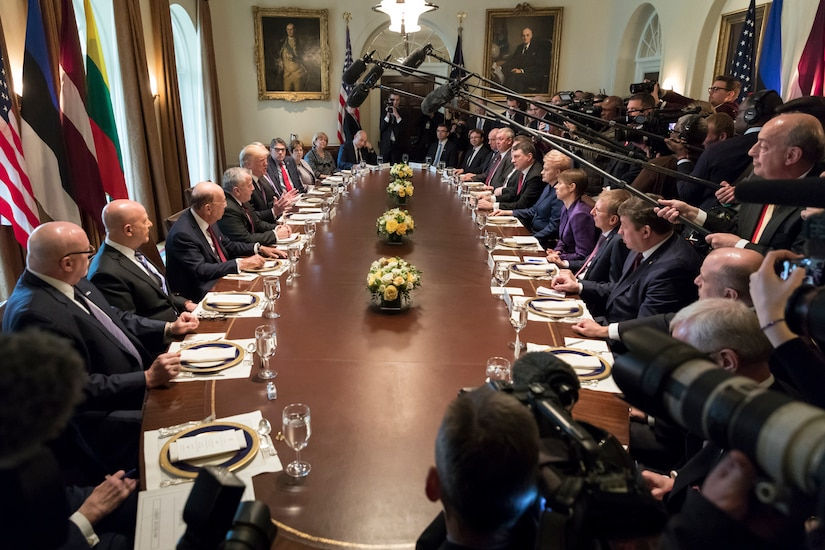 President Donald J. Trump sits at an oval table with other officials as media personnel hold microphones in the center of the table.
