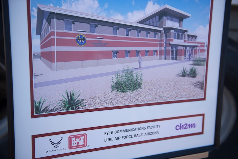 A concept image of the 56th Communications Squadron's future operations building sits in front of the site of its groundbreaking ceremony at Luke Air Force Base, Ariz., March 28, 2018. The building is being constructed in a joint effort between the 56th CS, the 56th Civil Engineer Squadron, the Army Corps of Engineers, and private contractors. (U.S. Air Force photo by Senior Airman Ridge Shan)