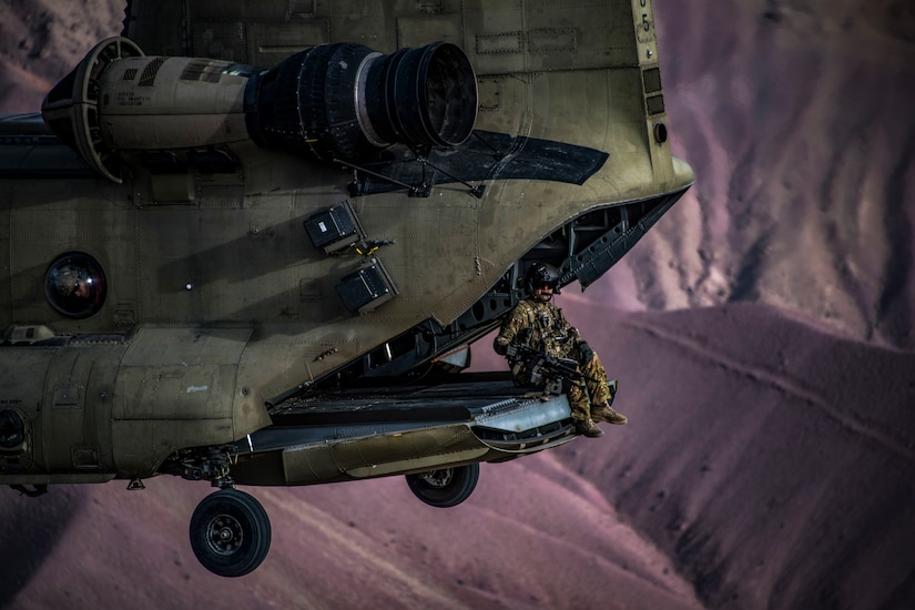 A soldier sits in the back of an open helicopter flying over dramatic purplish-brown hills.