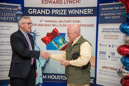 Retired Army Col. Edward Lynch (right) is congratulated by  James Jordan, Exchange chief financial officer, after receiving a $2,500 check to pay off his Military Star card balance at the Joint Base San Antonio-Fort Sam Houston Exchange April 4. Lynch was entered into the contest when he used his card last fall to make a purchase