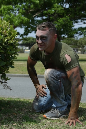 CAMP LESTER, OKINAWA, Japan – Lance Cpl. Kaiten DeArment crouches behind a bush dressed as a zombie during the American Red Cross hosted Zombie Run March 31 aboard Camp Lester, Okinawa, Japan.