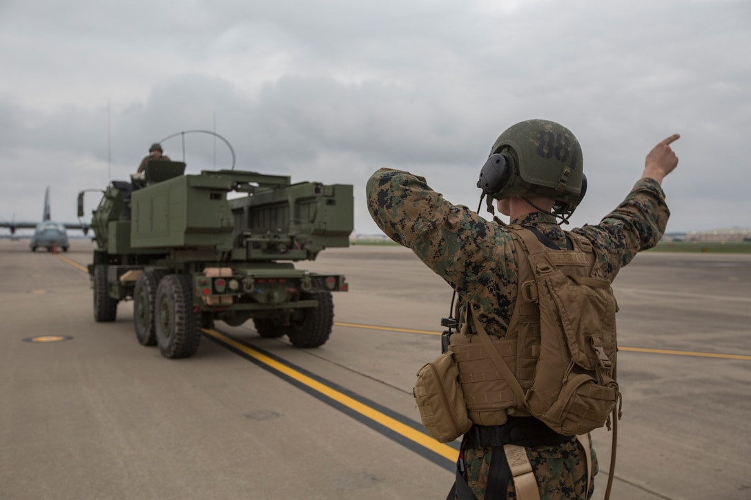 Marine Corps Sgt. Jeffery Hale, a launcher chief with Kilo Battery, 2nd Battalion, 14th Marine Regiment, directs a M142 High Mobility Artillery Rocket System (HIMARS) into position before being loaded onto an Air Force MC-130, on Fort Campbell, Ky., March 30, 2018. Marines from Kilo Battery flew from Fort Campbell to Dugway Proving Grounds, Utah, where they offloaded and fired four HIMARS missiles, demonstrating a unique capability that will give commanders more options to deal with threats when other options are not appropriate.